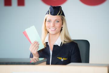freundliche flugbegleiterin mit boardkarten