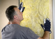 Worker installing fiberglass insulation on the wall