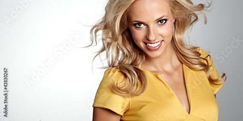 Portrait of a blond lady with a beautiful hair isolated on grey