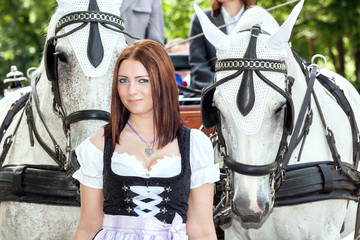 Woman in dirndl with a horse and wedding carriage