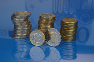 Euro. Greek euro coin with a stack of coins on blue background