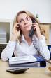 Frau telefoniert mit zwei Telefonen