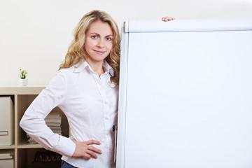 Frau im Büro lehnt an Flipchart