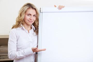 Frau zeigt auf leeres Flipchart