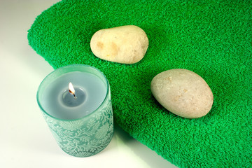 Candle and stones on green towel