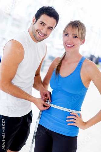Personal trainer measuring a woman