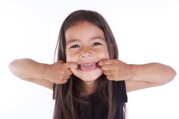 enfant fait des grimasses et tire la langue
