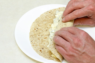 Hands Wrapping Egg Salad Wrap