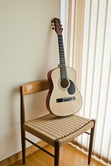 classical guitar leaning on a  chair