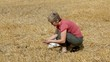Agricultural expert inspecting wheat field after harvest