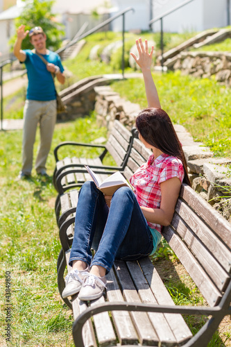 Woman waving to man sitting on bench