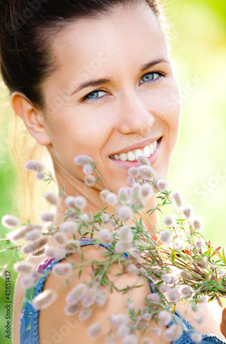 Beautiful woman with field plant in hands