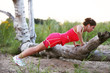 Woman doing push ups on the broken tree