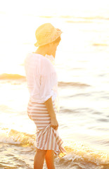 Beautiful woman wearing a hat in sunset light