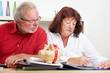 Rentnerpaar mit Sparschwein am Schreibtisch