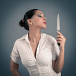 Sexy brunette woman holding a knife against dark background.