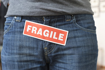 Midsection view of a person with a word 'Fragile' stuck on its jeans