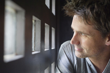 Close-up of a man looking through small windows
