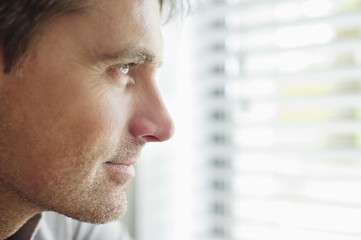 Close-up of a man looking through a window and thinking