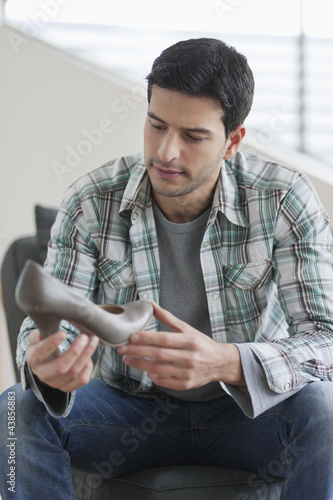 Man sitting on a couch and holding a high heel shoe