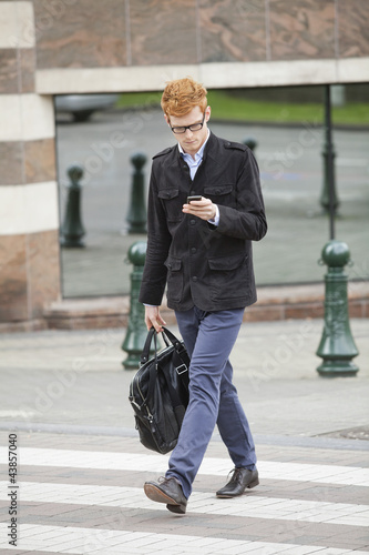 Businessman crossing a road while using a mobile phone