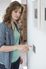 Woman pressing light switch on a wall