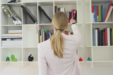 Woman taking out a book from shelf