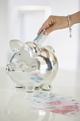 Person's hand putting money into a piggy bank