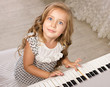 little girl sitting near the piano