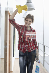 Woman cleaning a glass door and smiling