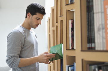 Man choosing a book from a bookshelf