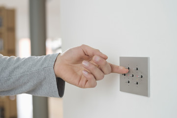 Close-up of a man's hand pressing light switch on a wall
