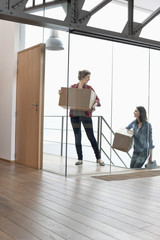 Two female friends carrying cardboard boxes at home