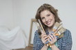 Portrait of a woman holding paintbrushes and smiling