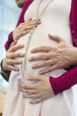 Close-up of a man's hand touching a pregnant woman's abdomen