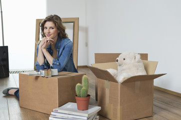 Woman leaning on a cardboard box and smiling
