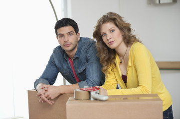 Couple leaning over cardboard boxes