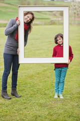 Woman and her son standing with a frame in a park