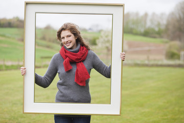 Portrait of a woman standing with a frame in a park