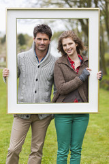 Portrait of a couple holding a frame