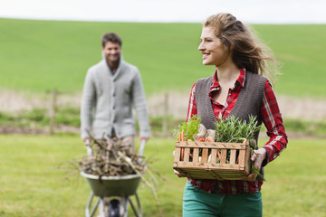 Woman holding a basket of vegetables with her husband collecting firewood