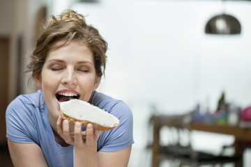 Woman eating toast with cream spread on it