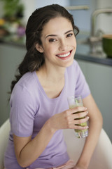Woman holding a glass of cold soup and smiling