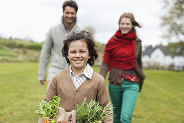 Portrait of a boy holding a basket of vegetables with his parents in a farm