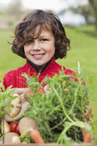 Happy boy with a crate of homegrown vegetables