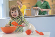 Cute little girl with slotted spoon and mixing bowl in the kitchen