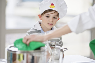 Boy helping his mother at dining table