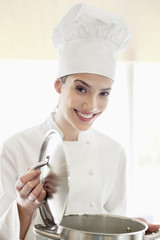 Happy female chef holding a saucepan