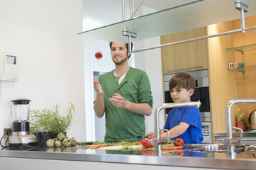 Man and son cutting vegetables in the kitchen