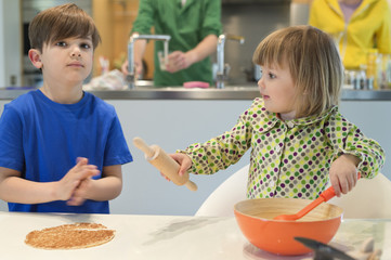 Children cooking in the kitchen with their parents in the background